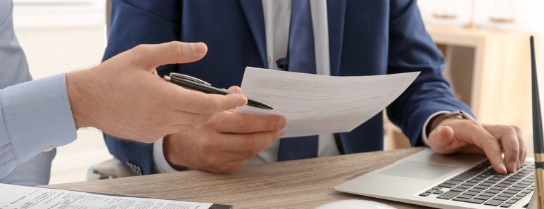 A suited man at a desk, handing over a legal document
