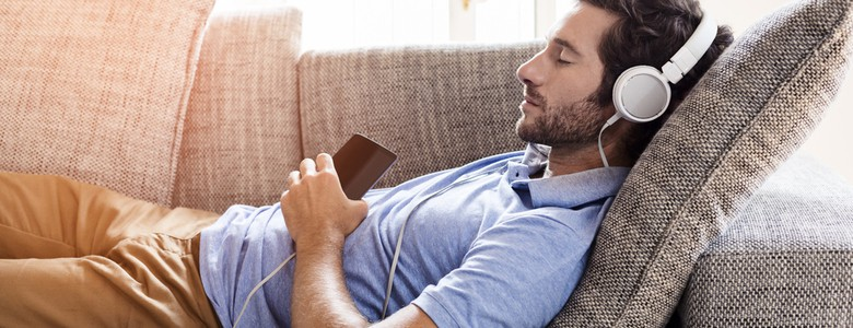 A young man lying on a sofa listening to music through headphones